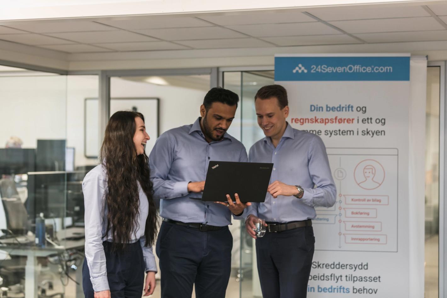 Tre ansatte hos Athene Group smiler mens de bruker 24SevenOffice