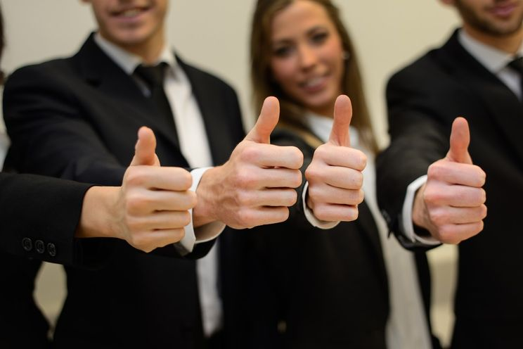 Business team i formelle klær holder tomlene opp i forgrunnen av bildet