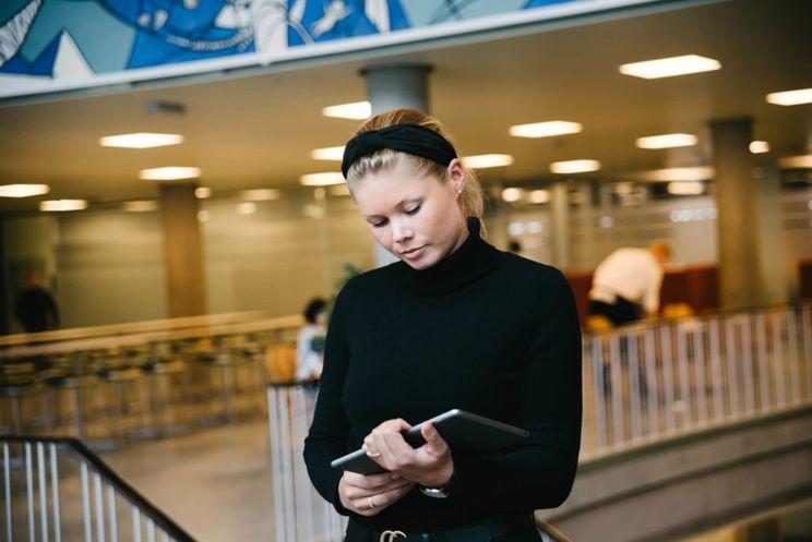 Kvinne i sort genser kikker ned på et nettbrett