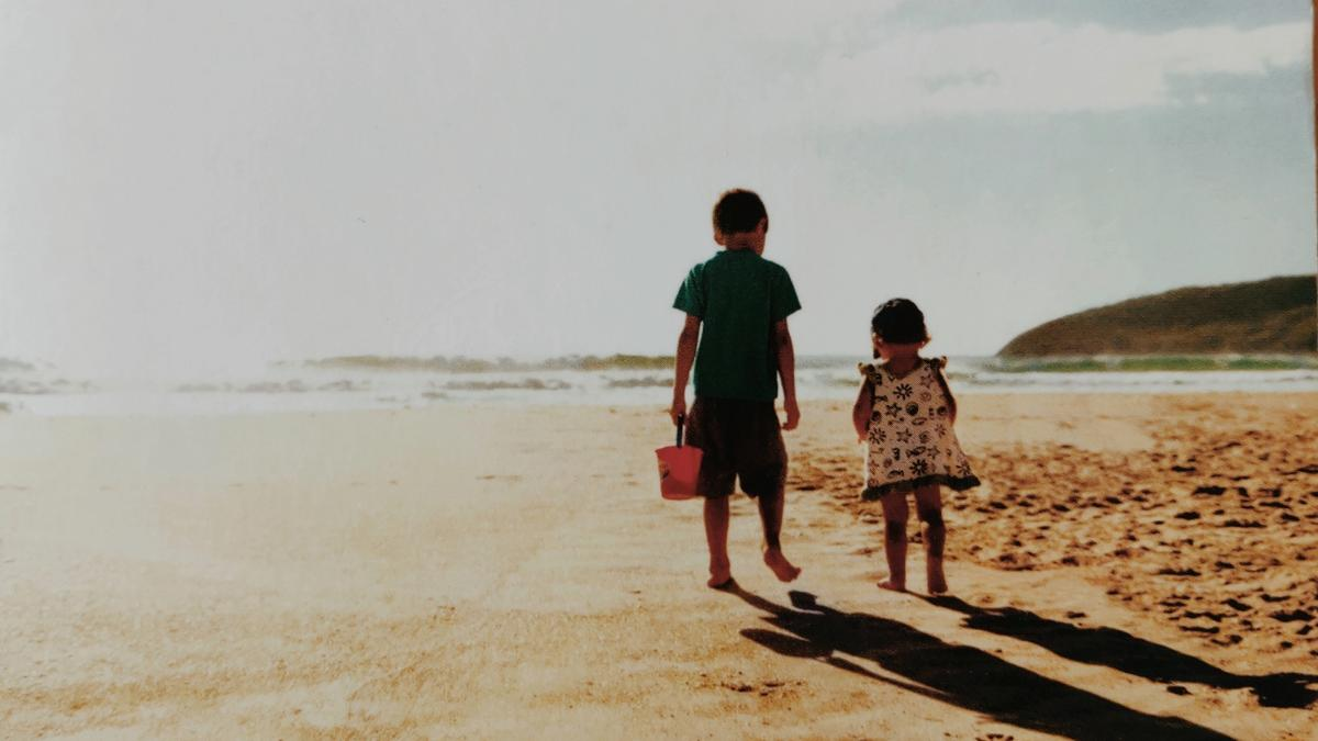 Cover detail from The Shell Seekers by Rosamunde Pilcher showing two children walking on a sandy beach