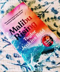 Malibu Rising Book on a blue and white background