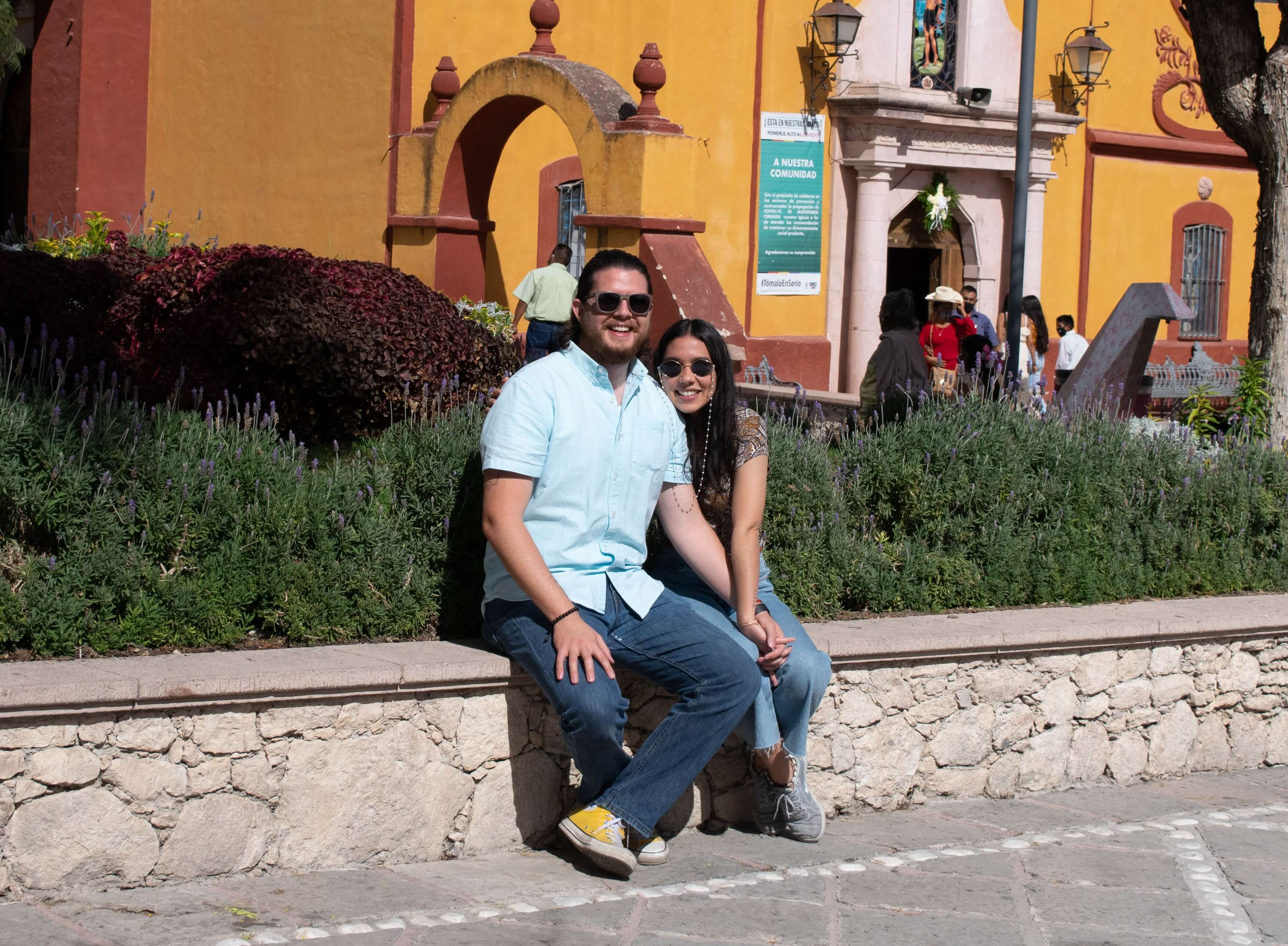Couple sitting on bench in front of yellow building