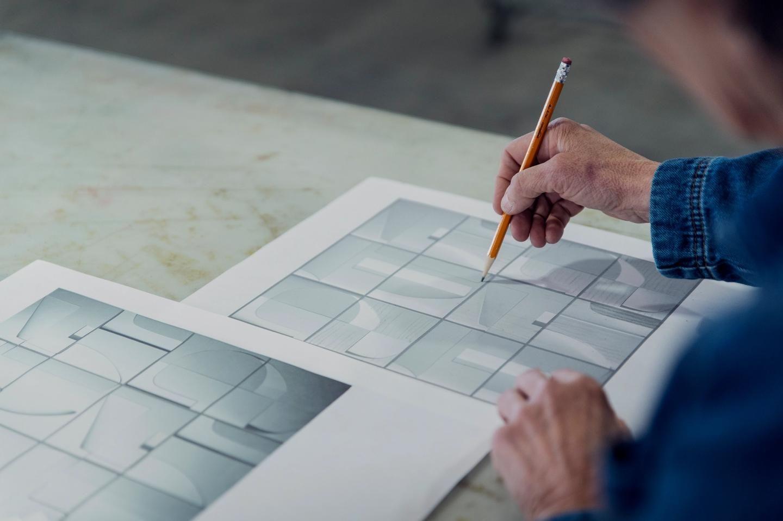 Artist, Mig Perkins reviewing a paper mockup