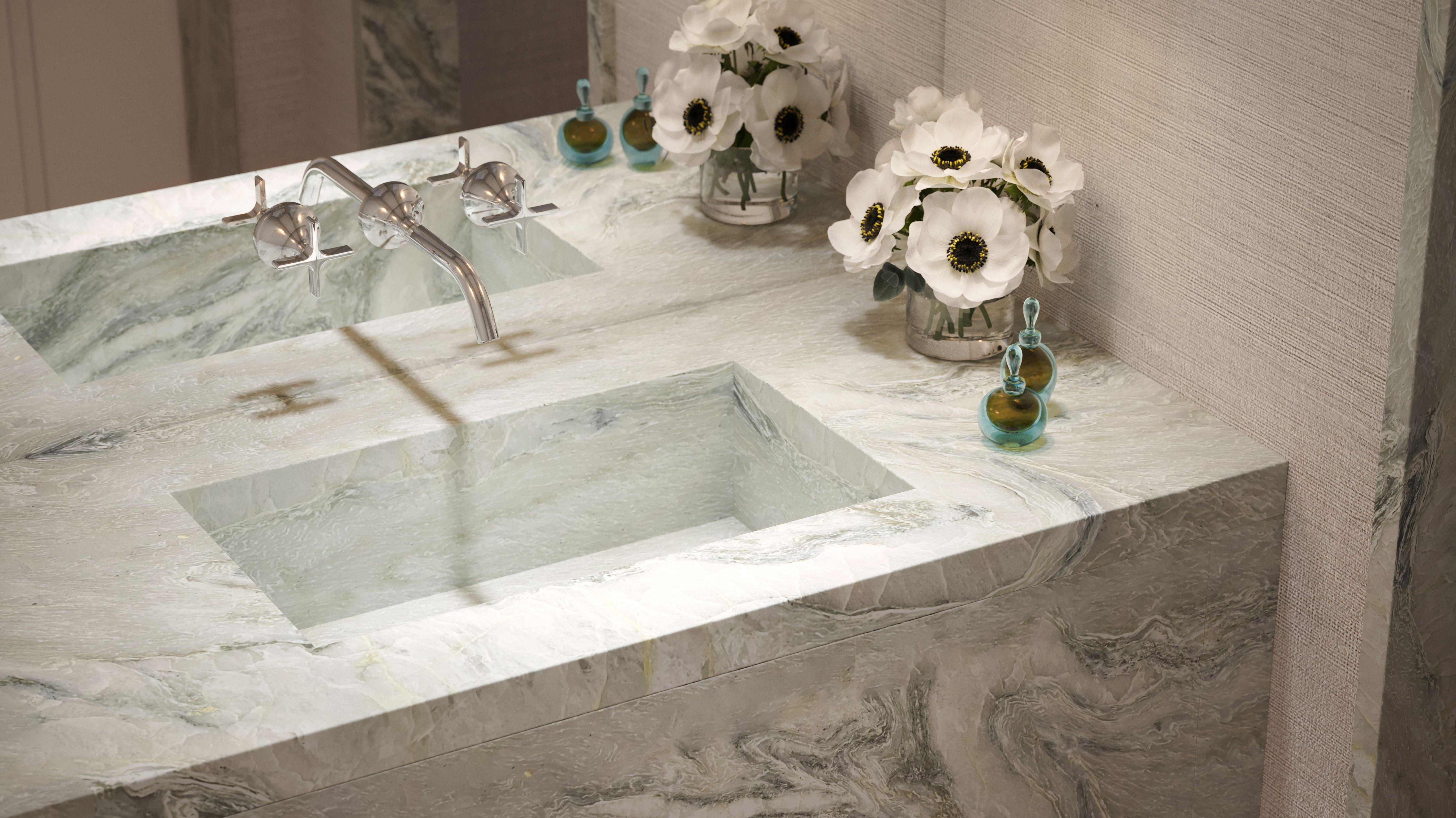 Powder rooms feature vanities clad in slabs of Maya Quartzite with custom integral sinks and Dornbracht Vaia plumbing fittings in polished nickel