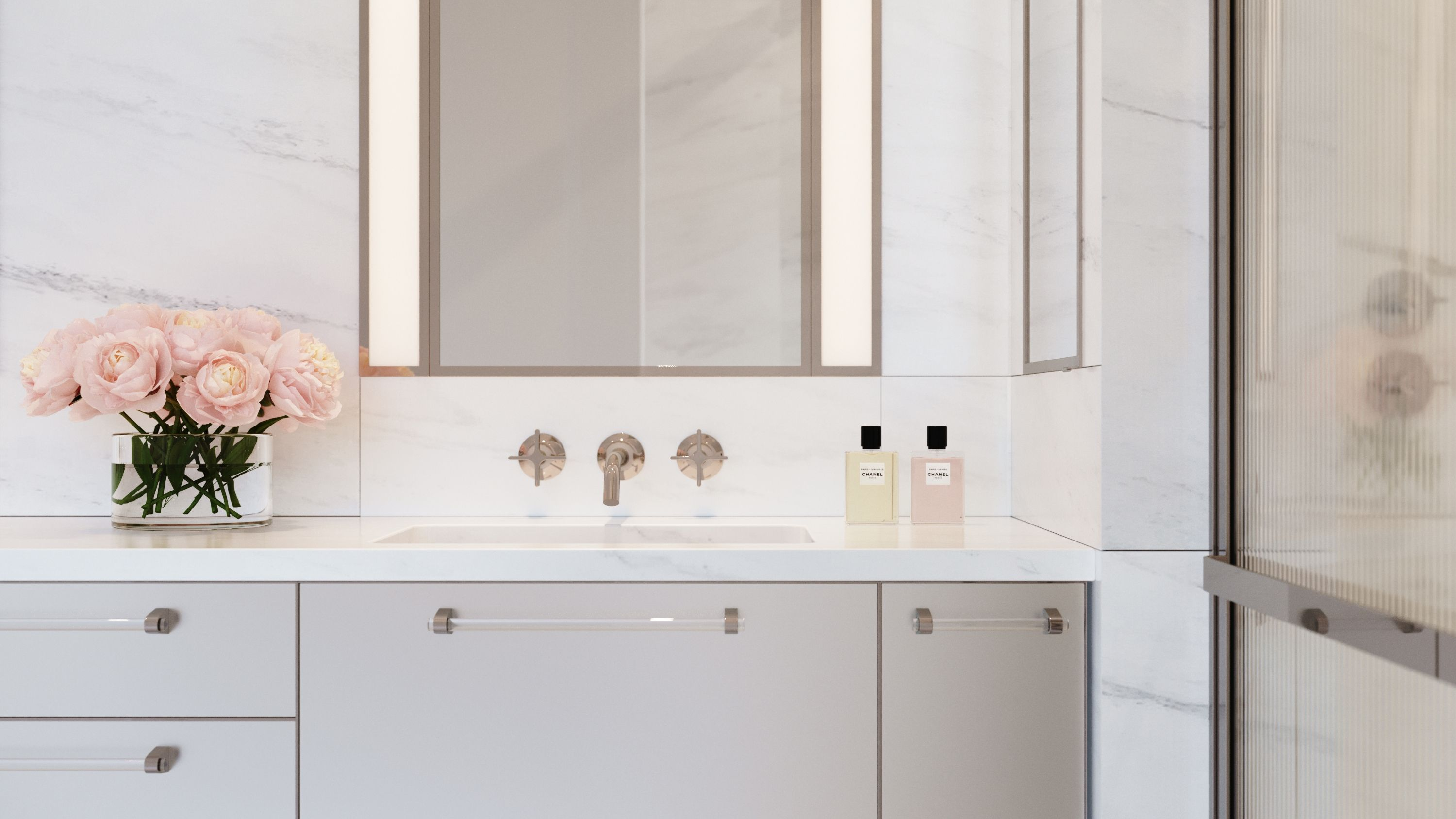 Luxurious details include Dornbracht Vaia fittings in polished nickel, custom recessed medicine cabinets, and vanities clad in acid etched glass