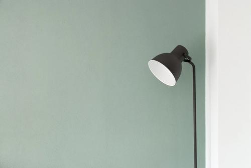 Floor lamp near a green wall