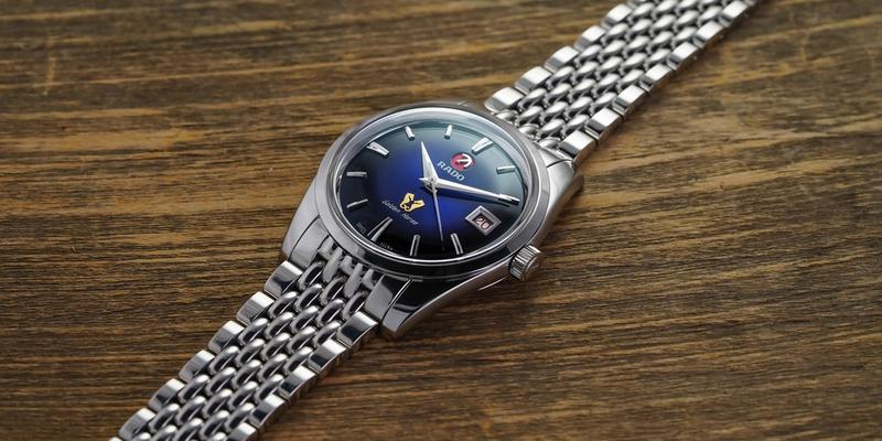 Rado Golden Horse blue dial on bracelet laying on wooden table