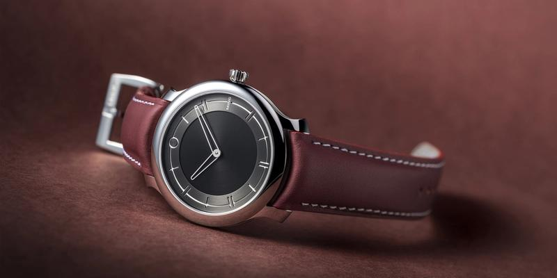 Ming 27.01 watch on brown leather strap laying on side on table.