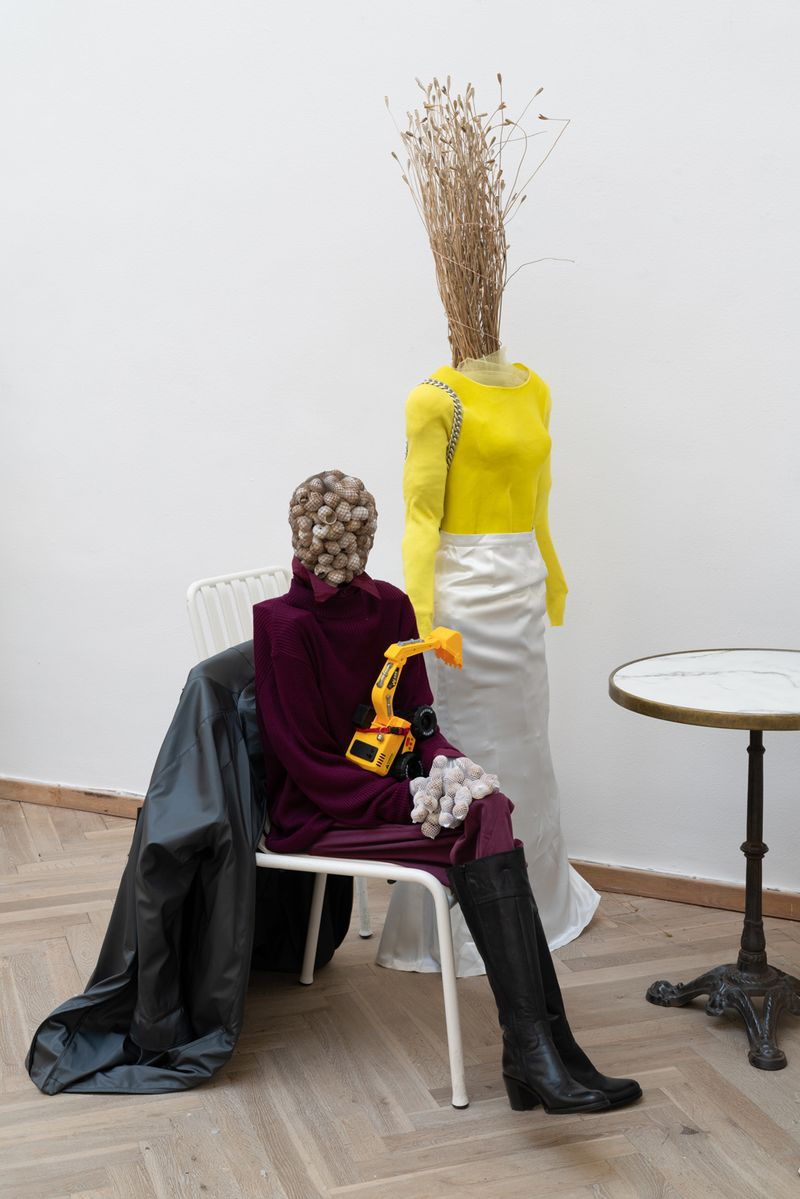 Rasmus Myrup, Limgrim's Mother and Limgrim, 2020, Snail shells, Pantyhose, gloves, jacket with embriodered patches, shirt, sweater, pants, boots, wooden structure and Toy excavator, cat collar with bell, photo: David Stjernholm