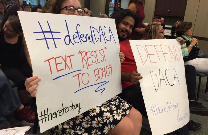 """Two people at a town hall holding up """"test resist to 50409"""" and """"defend DACA"""" signs"""
