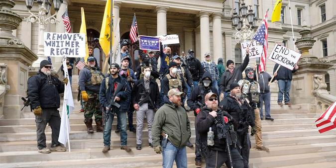 Rifle strapped protesters demand an end to the COVID lockdown on the steps of the Michigan capitol building
