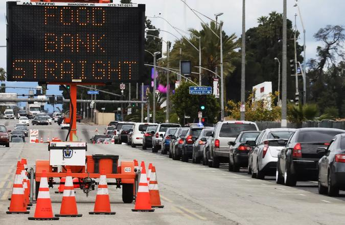 """Line of traffic with an advisory sign that reads """"food bank straight"""""""