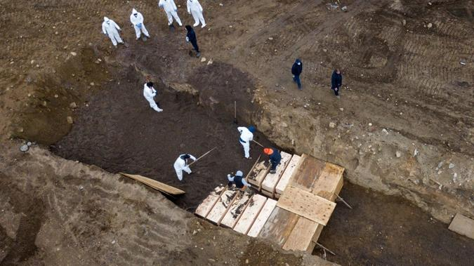 Overhead view depicting Coronavirus victims being buried in coffins in a mass grave in New York.