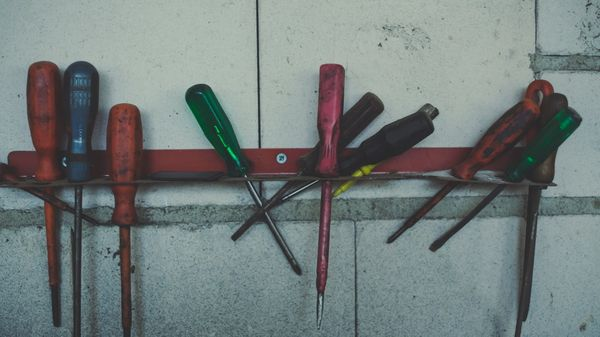 Assortment of worn screwdrivers haphazardly set in a rack