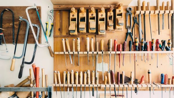 Organized wood working tools on a wood shop wall