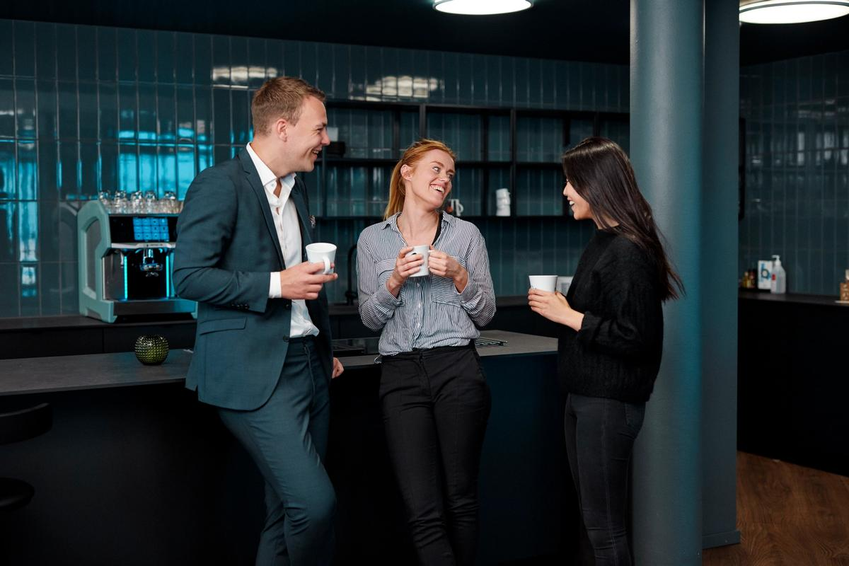 Tre personer ved kaffemaskinen som prater og ler