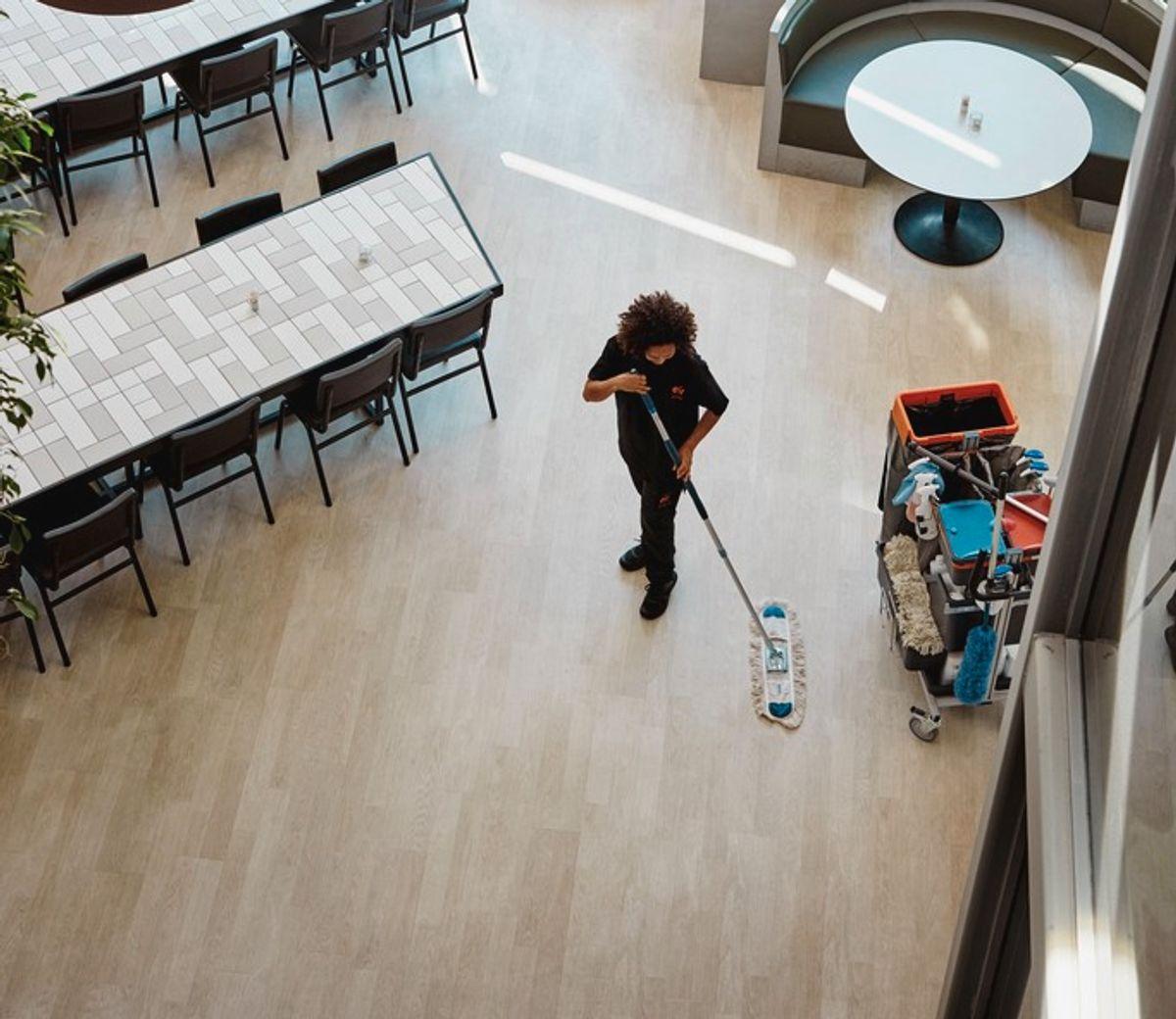 Renholder som vasker gulv