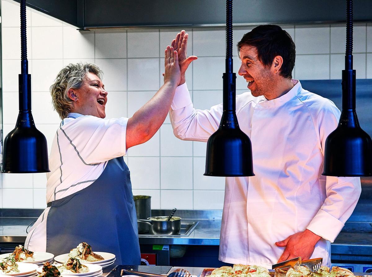 To glade kokker som gir high five på kjøkkenet