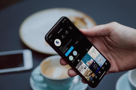 En hånd som holder en iphone med instagram kontoen til 4Service