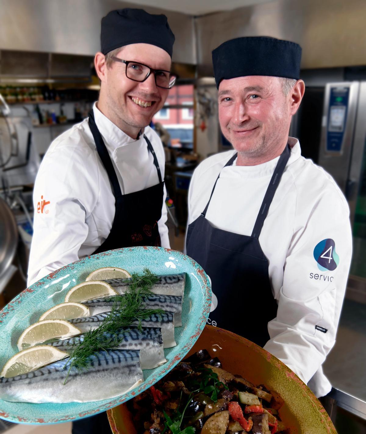 To kokker viser frem fat med mat
