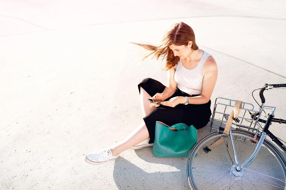 Eine Frau sitzt neben ihrem Fahrrad auf dem Boden
