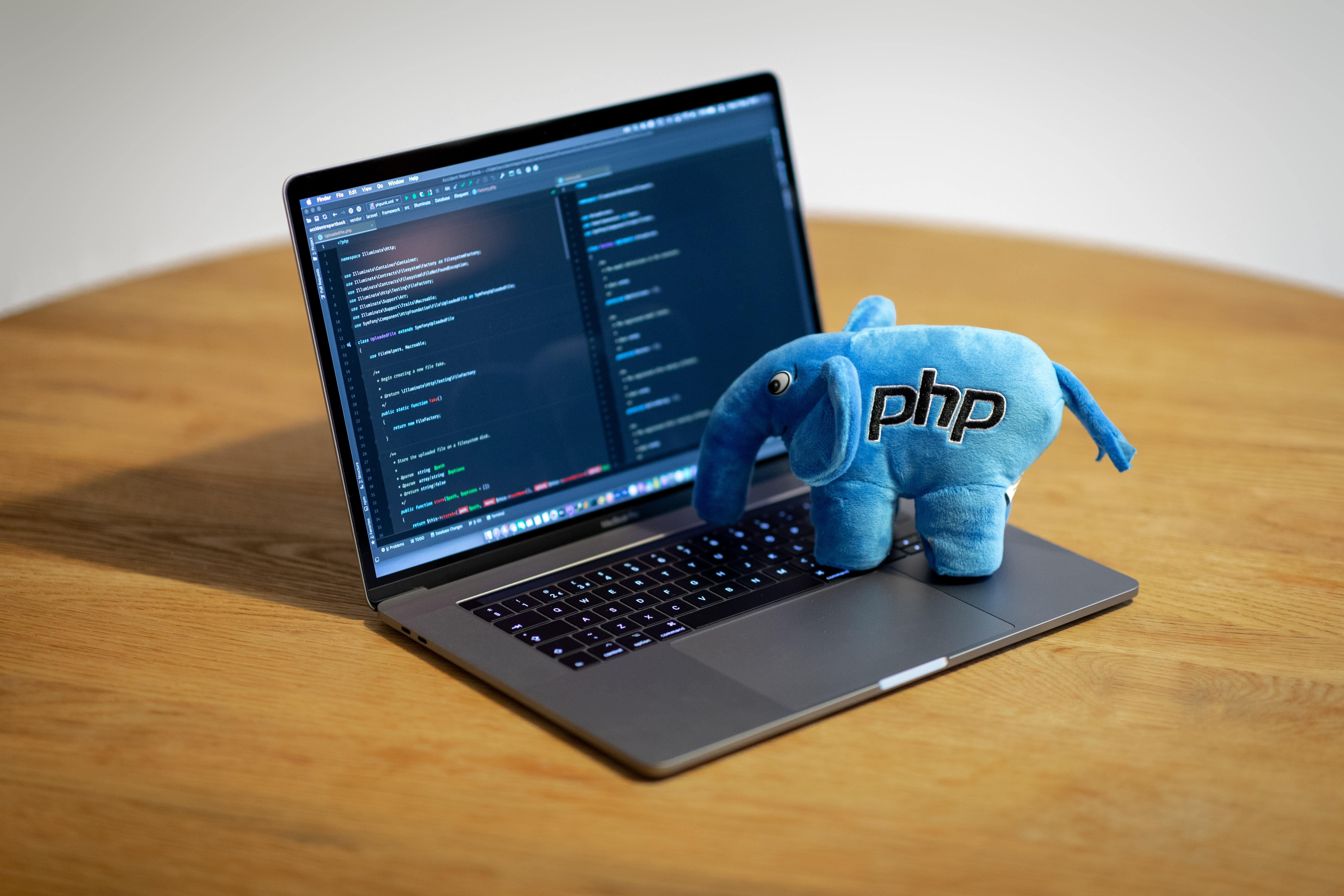 a PHP plush on top of a laptop
