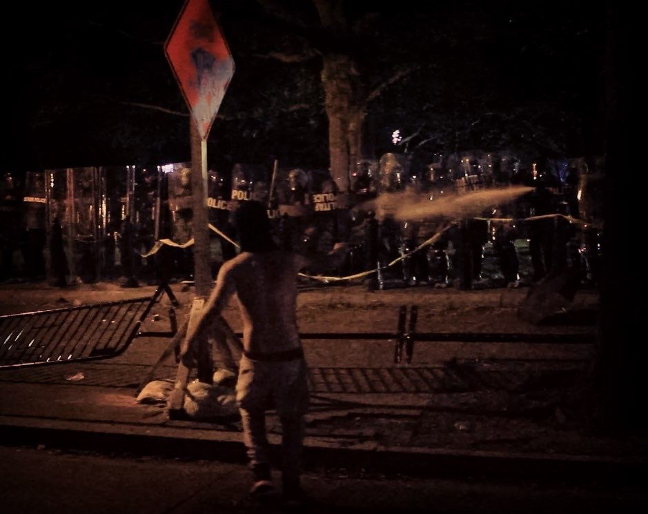 tear gas from a line of police against a single protester