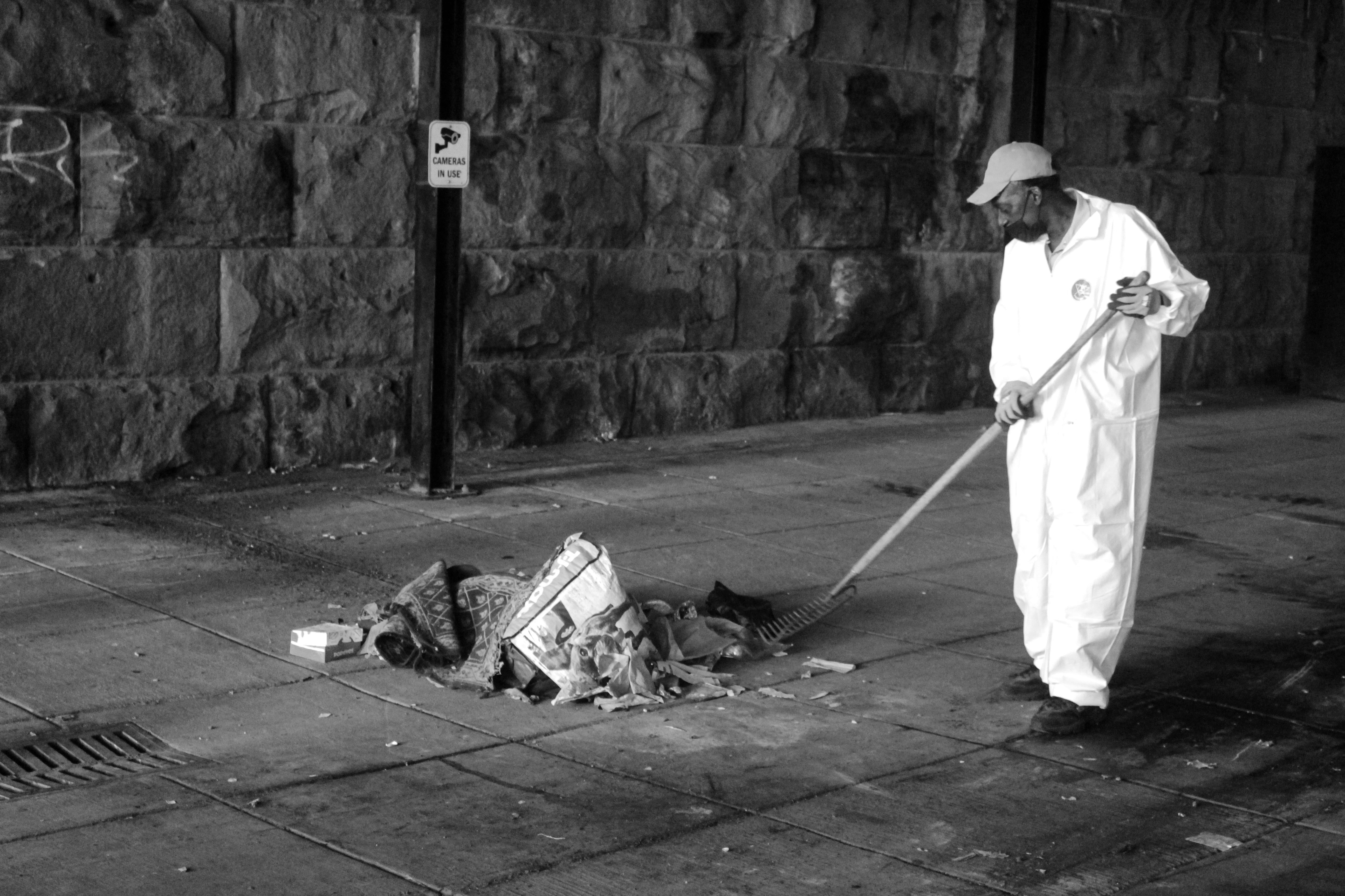 A DC city worker sweeps together a pile of belongings
