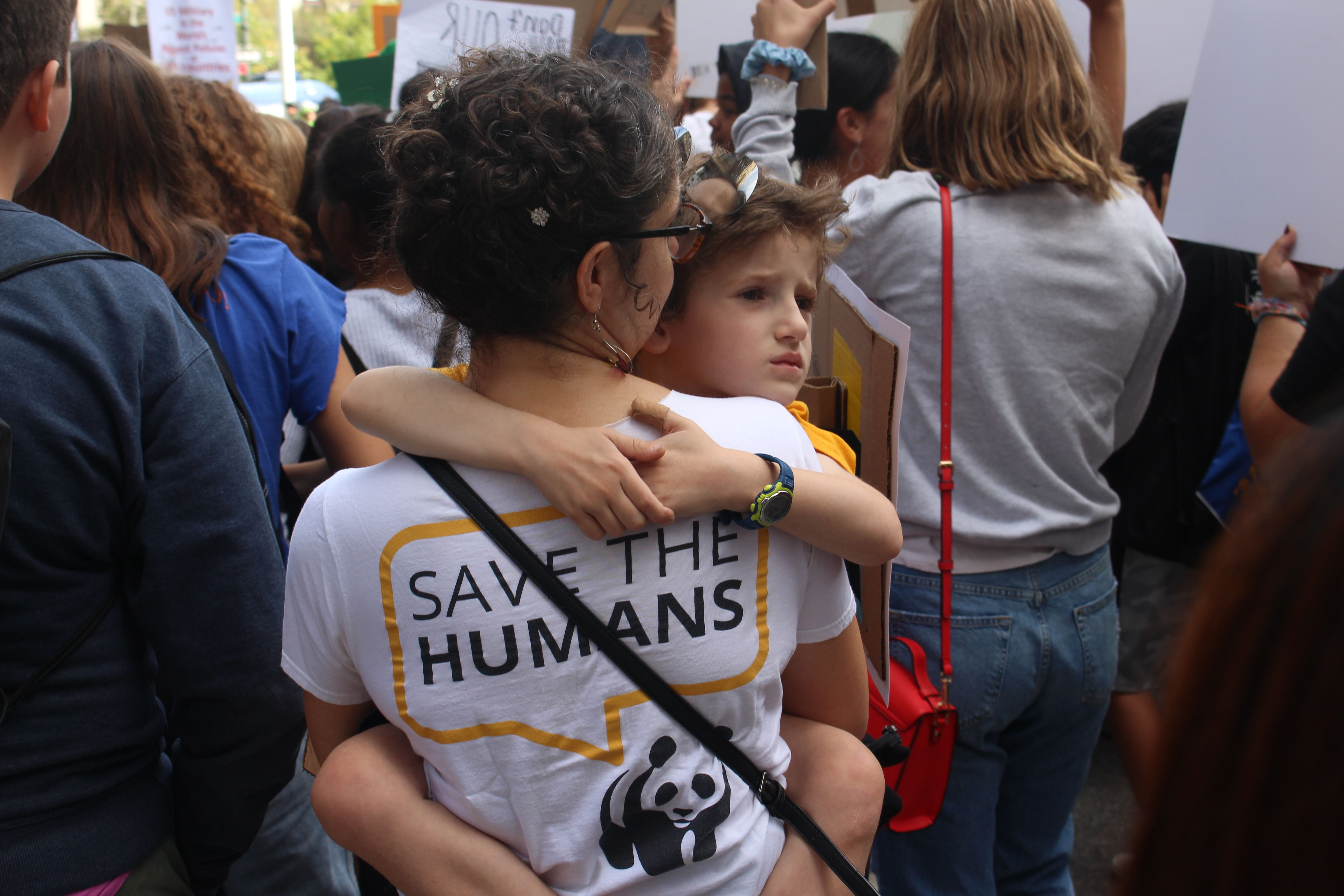 mother holding her child wearing save the humans shirt