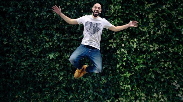 Illustrasjonsbilde av en glad mann som hopper med planter i bakgrunnen, tatt av Jonathan Sebastiao fra Unsplash