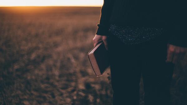 Mann som står på et jorde med en bok i hånden. Illustrasjonsbilde tatt av Priscilla Du Preez fra Unsplash