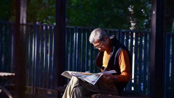 Eldre mann med orange genser og svart vest sitter på en benk i sola å leser avisen. Illustrasjonsbilde tatt av  Mark Hang Fung So fra Unsplash
