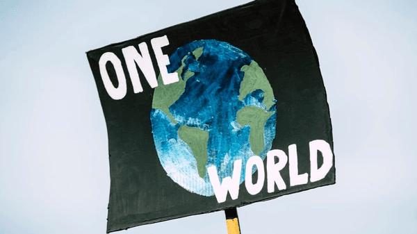 """Plakat med bilde av Jorda og teksten """"One World"""", med himmelen som bakgrunn."""