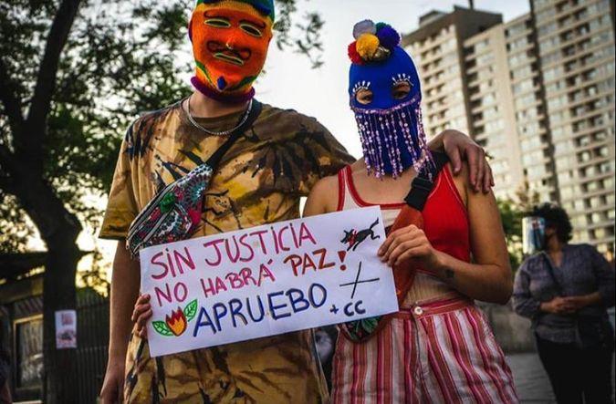 kvinne holder opp en plakat i en demonstrasjon i Chile