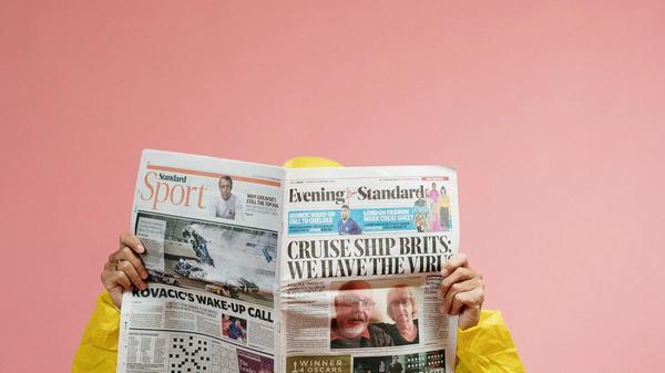 person i gul drakt leser avisen
