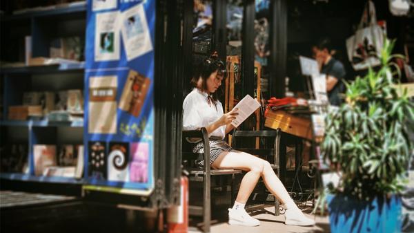 Kvinne leser avisen utenfor en butikk