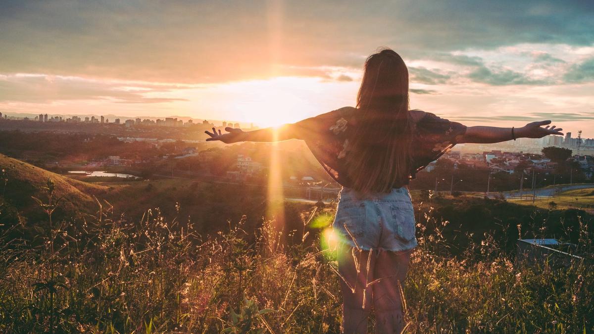 Kvinne står med utstrakte armer å ser på solnedgangen