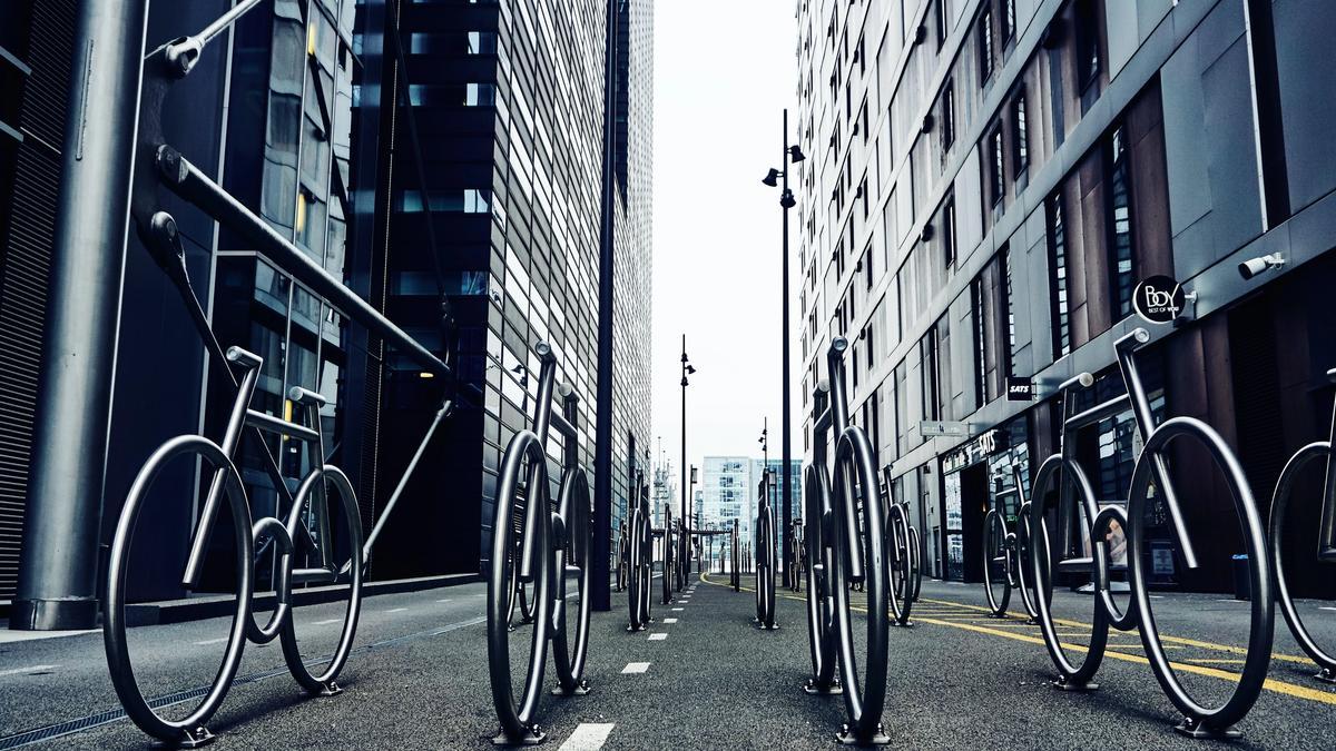 Illustrasjonsbilde av grå bygninger og sykler i stål som står på rad i en bygate tatt av Alexey Topolyanskiy fra Unsplash