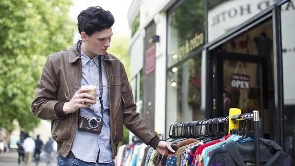 Ung mann ser på noen klær i en gate