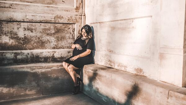 Illustrasjonsbilde av gravid kvinne i svart kjole som sitter i et hjørne tatt av Chris fra Unsplash