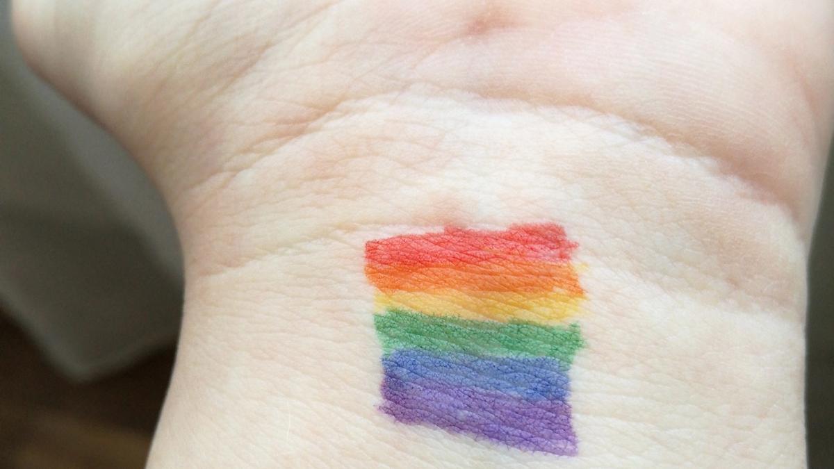 hånd med LGBTQ+ flagget på. Illustrasjonsbilde tatt av chris_photography fra Unsplash