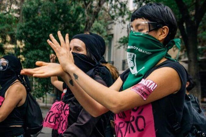 To kvinner med svart hår som står å demonstrer i kledd svarte klær og rosa tørkler med skrift på. Den ene kvinnen har kort hår og har på seg et grønt bind foran munnen.  Bilde tatt av Isidora Alejandra Torrealba