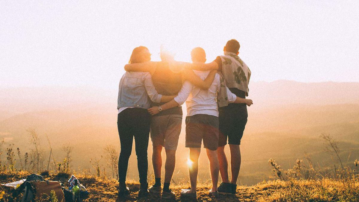 Foto av fire venner som holder rundt hverandre og ser ut mot solnedgangen