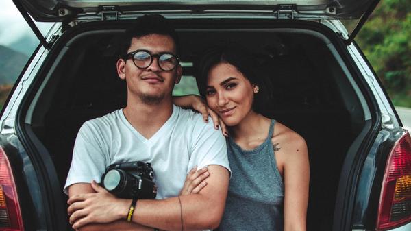 to venner sitter i en bil og ser på kamera