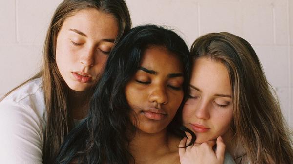 Tre jenter som holder rundt hverandre