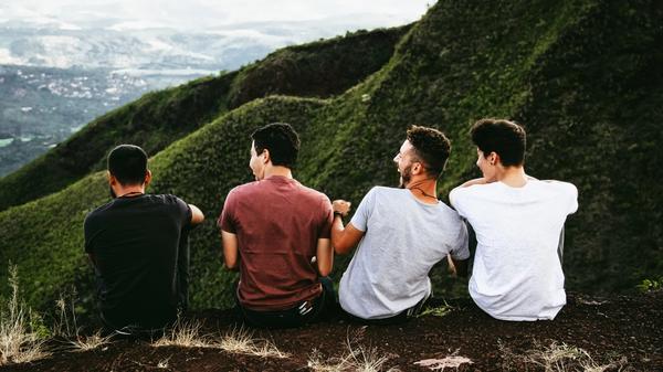 Foto av fire venner som sitter på et fjell sammen og ler