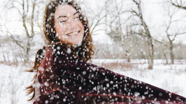 Smilende kvinne ute i snøen