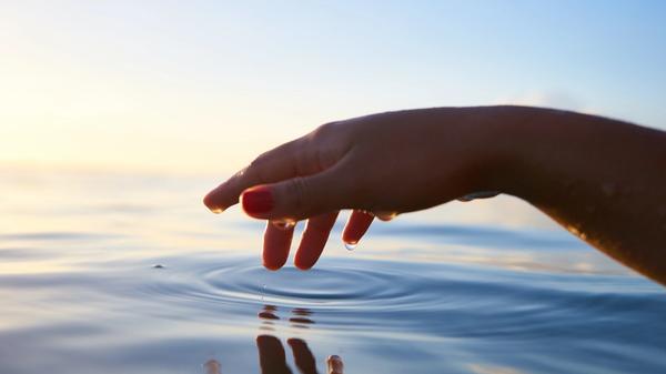en hånd tar på havet