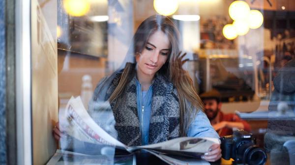 Kvinne leser avisen på en kafé