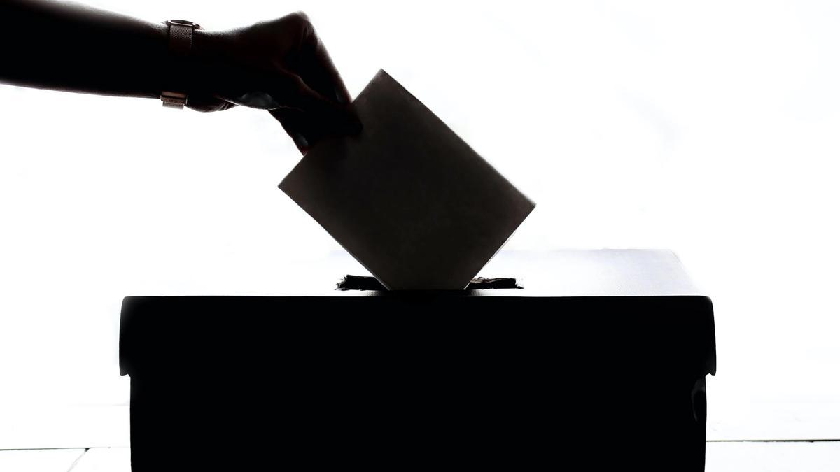 Illustrasjonsbilde som viser en hånd som legger en stemmeseddel i en boks. Bildet er svart hvitt .Tatt av Element5 Digital fra Unsplash
